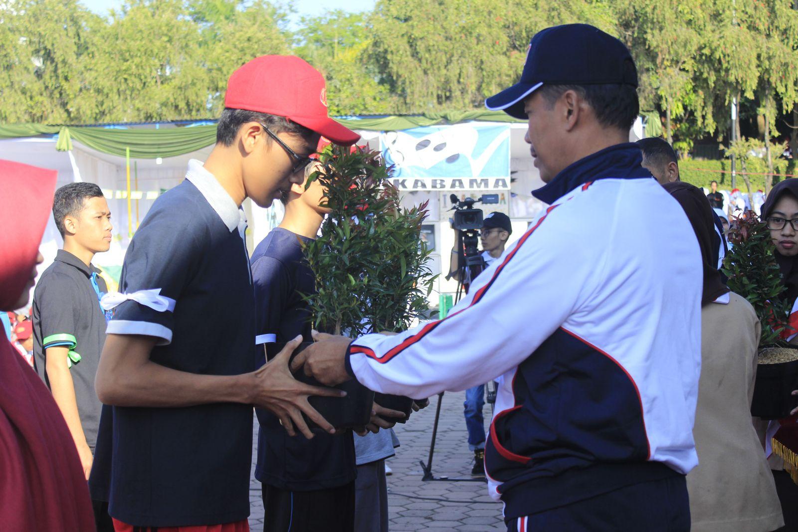 Simbolis: Rektor UMM fauzan menyerahkan tanaman kepada salah satu perwakilan mahasiswa peserta student day 2016 di heilpad UMM (Desita/Bestari)